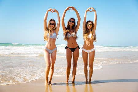 Schöne Mädchen im Strand machen Herzen mit ihren Händen Standard-Bild - 77040840