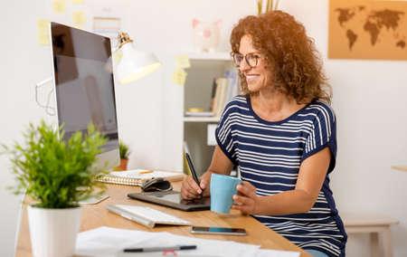 Middle age designer working on a desktop with a stylus pen Banco de Imagens