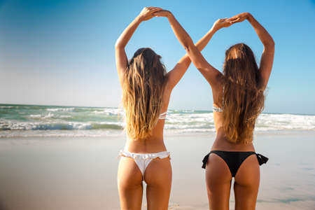 Beautiful girls in the beach giving her hands together Banque d'images