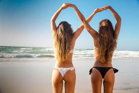 Mooie meisjes op het strand die haar handen samen geven Stockfoto