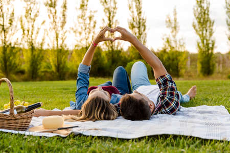 Happy couple in love, lying on the park and enjoying the day together 版權商用圖片