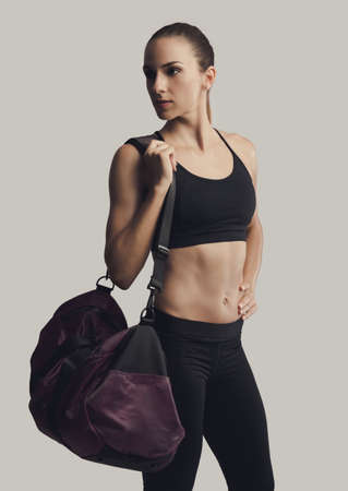 Portrait of sporty young woman posing with a gym bag,  against a gray background