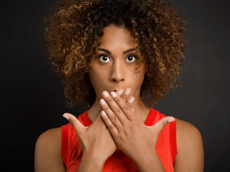 Portrait of a beautiful African American woman covering her mouth with hands Banco de Imagens