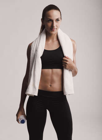 Portrait of sporty young woman holding a water bottle and towel, posing against a gray background Banco de Imagens