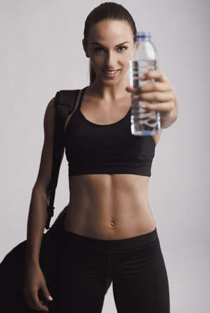 Portrait of sporty young woman holding a water bottle, against a gray background