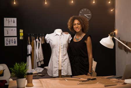 Portret van een jonge modeontwerper die aan haar atelier werkt Stockfoto