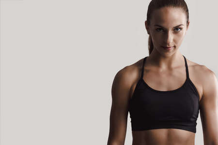 Portrait of a fitness woman posing against a gray background