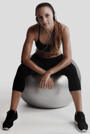 Shot of a beautiful young woman sitting on swiss ball after the train Stock Photo