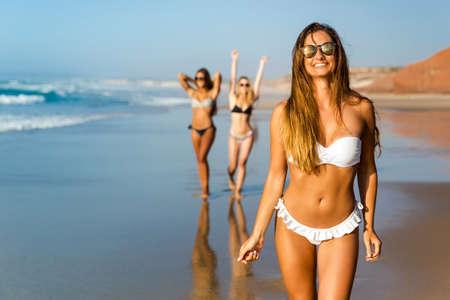 Three beautiful girls having fun on the beach Stock Photo