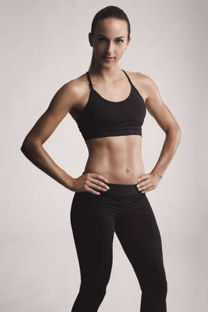 Portrait of sporty young woman with muscular body looking at camera confidently Stock Photo - 81050458