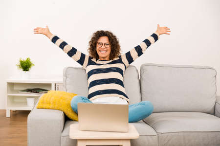 Beautiful happy woman with arms open sitting on the sofa with a laptop