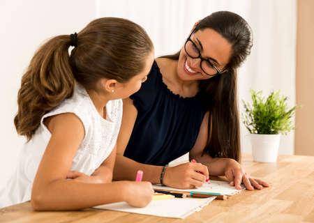Joven madre ayudar a su hija con la tarea en casa Foto de archivo - 81786545
