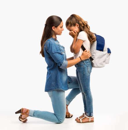 Moeder troost haar dochtertje op haar eerste schooldag Stockfoto