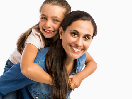 Mother giving her Daughter a ride On her back while playing Stock Photo