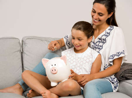 Mother and daughter putting coins into a piggy bank