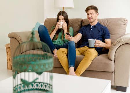 Jeune couple sur le café canapé potable tout en regardant la télévision Banque d'images