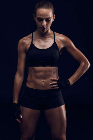 Studio portrait of a sporty young woman posing against a dark background