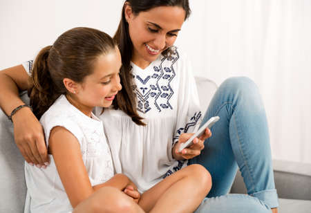 Beautiful Mom showing to her daughter something on her phone Foto de archivo