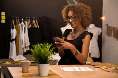 Een jonge modeontwerper op haar atelier die een telefoongesprek voert Stockfoto