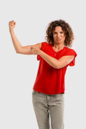 Portrait d & # 39 ; une brune brune moyen pointant vers son bras musculaire Banque d'images - 84672321