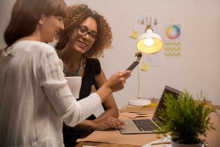 Twee jonge ondernemersvrouwen, en manierontwerper die aan haar atelier werken