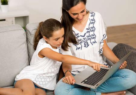 Moederonderwijs Dochter die thuis met een laptop werkt Stockfoto
