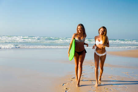 Best friends enjoying the summer, running on the beach with a surfboard Banque d'images