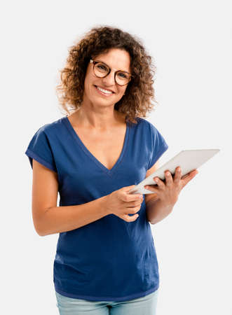 Beautiful middle aged woman working on a tablet Фото со стока