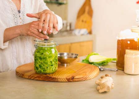 Preparing fermented preserved vegetables. Jars of cabbage kimchi and sauerkraut sour cabbage.