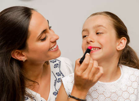Mother playing with her daughter applying lipstick Stock Photo