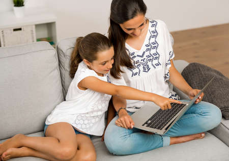 Mom teaching Daughter working with a a laptop at home 스톡 콘텐츠