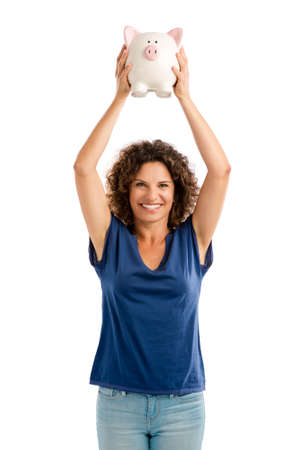 Portrait of a happy middle aged woman holding a Piggybank over her head Zdjęcie Seryjne