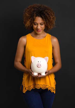 Portrait of a beautiful African American woman holding a Piggybank Zdjęcie Seryjne