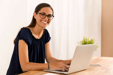Portrait of a happy businesswoman sitting at her desk in a home office Banque d'images