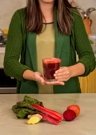 Woman holding a glass of red juice. Preparing a detox juice.