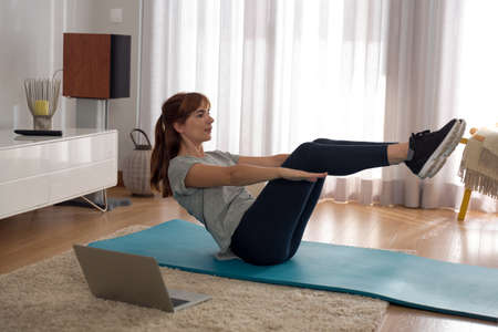 Full length shot of a woman doing exercise at home Standard-Bild