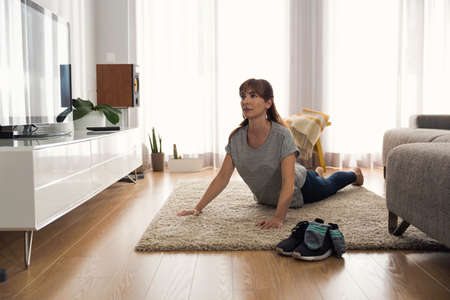 Full length shot of a woman doing exercise at home Stock Photo