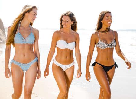 해변에서 산책을 즐기는 여름을 즐기는 아름다운 소녀 스톡 콘텐츠