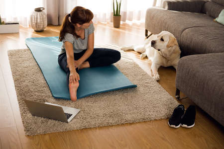 Shot of a woman doing exercise at home with her dog Foto de archivo