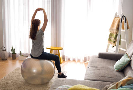 Full length shot of a woman doing exercise at home with a swiss Ball