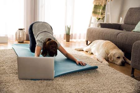 彼女の犬と家で運動をしている女性のショット 写真素材