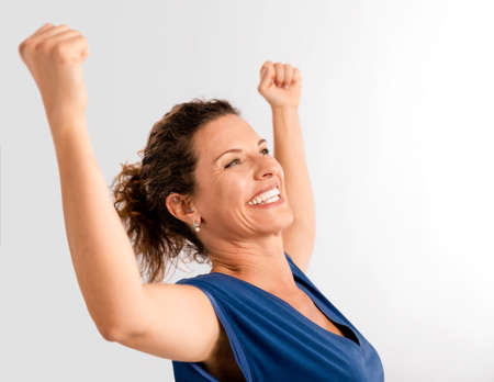 Portrait of a happy middle aged brunette with arms up expressing victory