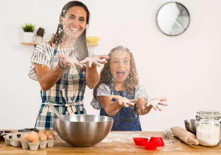 Ontsproten van een moeder en een dochter die pret in de keuken hebben en een cake leren te maken Stockfoto - 90413332