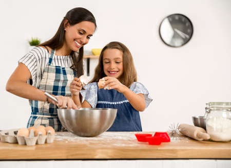 Shot of a mother and daughter having fun in the kitchen and learning to make a cake Stockfoto - 90425592