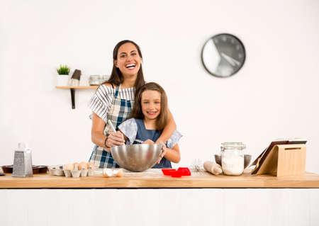 Ontsproten van een moeder en een dochter die pret in de keuken hebben en een cake leren te maken Stockfoto - 90996559