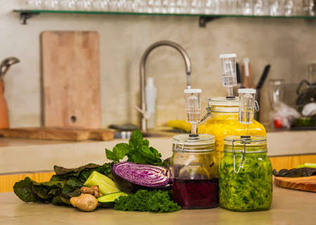 Preparing fermented preserved vegetables. Jars of cabbage kimchi and sauerkraut sour cabbage.   Banco de Imagens