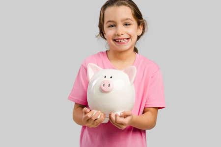 Cute little girl holding a piggybank with her savings Zdjęcie Seryjne