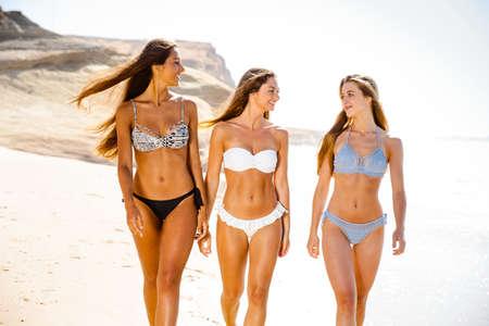 Beautiful girls enjoying the summer giving a walk on the beach