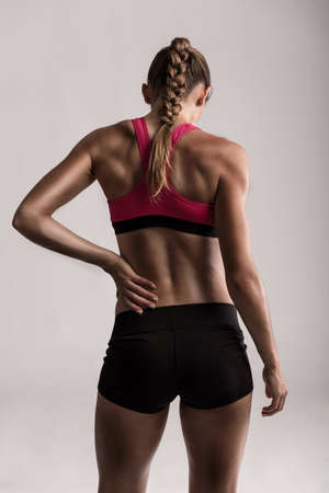 Studio shot of a sporty young woman holding her lower back in pain Standard-Bild