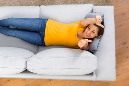 Top view of a beautiful and happy young woman lying on a sofa  版權商用圖片